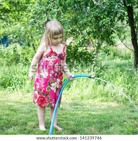Girl playing with water hose - stock photo