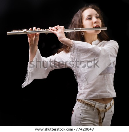 girl plays the flute on a black background - stock photo