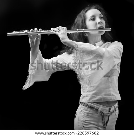 girl plays the flute on a black background.black-and-white photo - stock photo