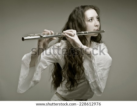 girl plays the flute on a grey background.sepia - stock photo