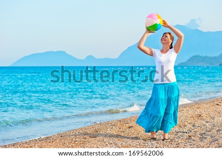 girl plays with a beach ball near the sea - stock photo