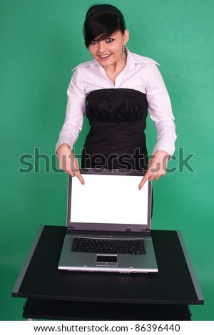 Girl pointing at blank laptop screen. - stock photo