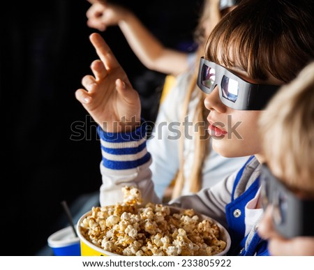 Girl pointing while watching 3D movie with siblings at cinema theater - stock photo