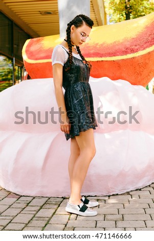 Girl posing in a park in glasses near a large marshmallow and orange