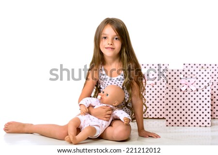 Girl posing in studio with a doll in hands. Isolated on white background. - stock photo