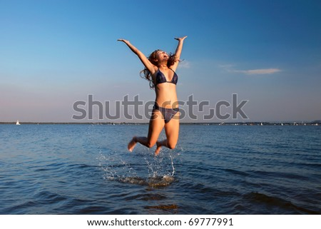 girl posing in the Water at sunset - stock photo
