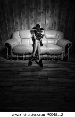 girl posing on a white sofa in a black dress - stock photo