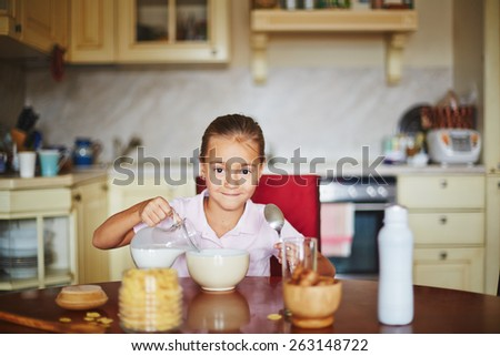 Girl pouring milk and looking at camera