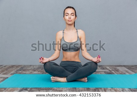 Girl practicing yoga isolated on a grey background - stock photo