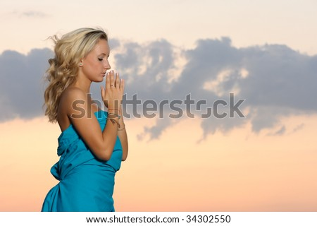 girl praying at sunset - stock photo
