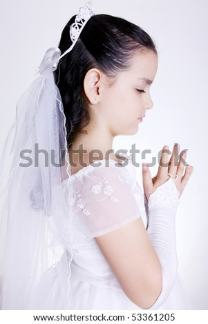 Girl praying with her hands clasped and white dress. First Communion - stock photo