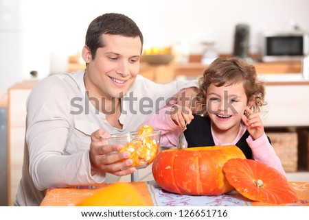 Girl preparing pumpkin with father - stock photo