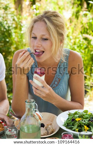Girl putting a spoon with yoghurt in her mouth - stock photo