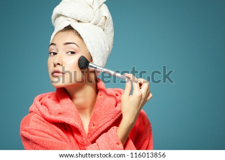 girl putting rouge in the morning over blue background - stock photo