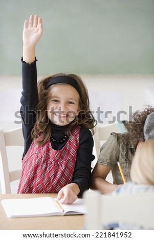 Girl raising hand in class - stock photo