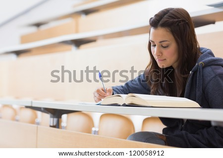 Girl reading a book and writing notes at the lecture hall - stock photo