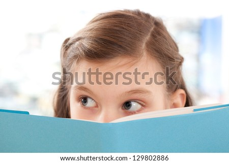 Girl reading a book at school and looking up - stock photo