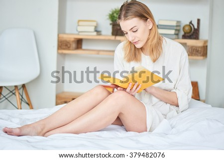 Girl reading a book in his house on the bed