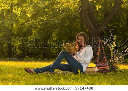 Girl reading a book in park - stock photo
