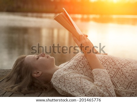 Girl reading a book in sunset - stock photo