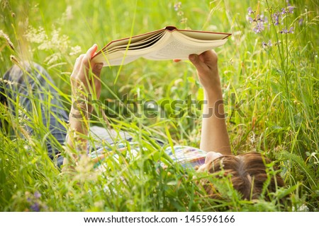 girl reading a book lying in the tall grass - stock photo
