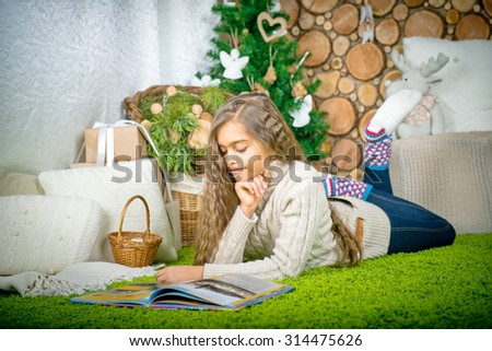 girl reading a book lying on the carpet. leisure winter evening - stock photo