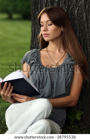 Girl reading a book on grass near tree in park