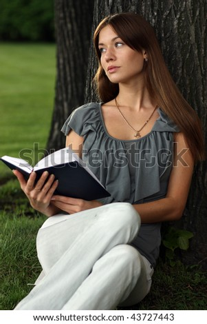 Girl reading a book on grass near tree in park - stock photo