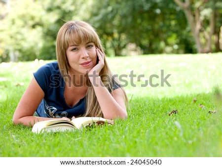 girl reading a book on the floor - outdoors