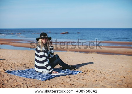 girl reading a book sitting on the beach