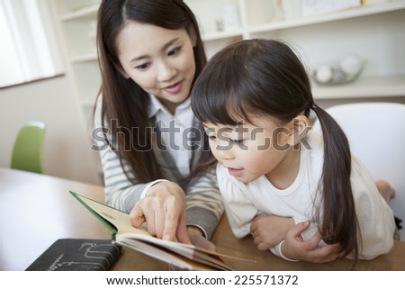 Girl reading a book with her mother - stock photo