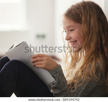 Girl reading book. Child with book at home
