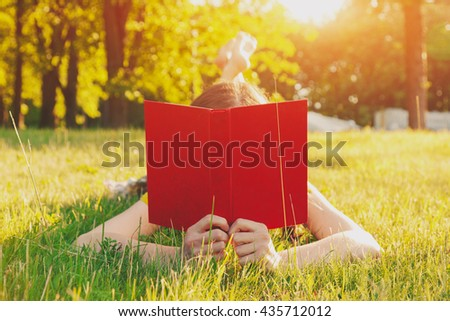 girl reading book lying in warm summer grass - stock photo