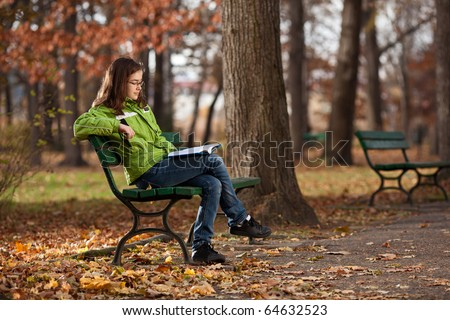 Girl reading book sitting in park