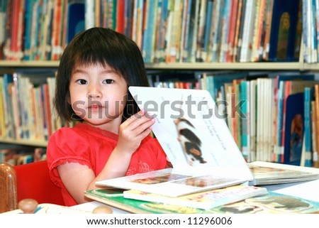 girl reading children's book at library - stock photo