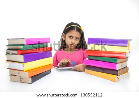 Girl reading e-book surrounded by several books, isolated on white background - stock photo