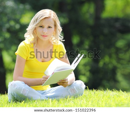Girl reading the book. Blonde beautiful young woman with book sitting on the grass. Outdoor. Sunny day. Looking at the camera