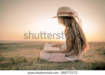 Girl reading the book on rural landscape, sepia toned image - stock photo