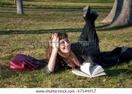 Girl reading while lying in a park on the grass - stock photo