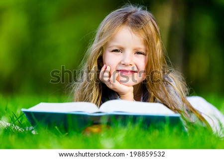 Girl reads interesting book lying on the green grass in the summer park