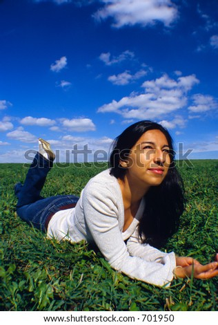 Girl relaxes on a grass field.