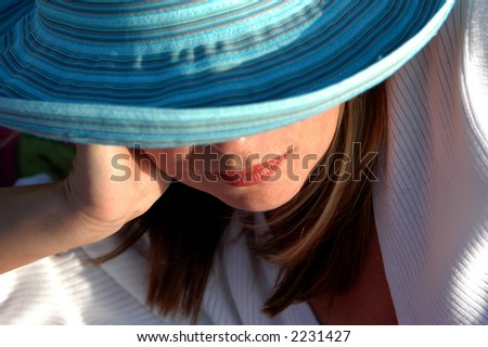 Girl relaxing at beach in sun hat. - stock photo