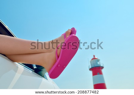 Girl Relaxing in a Car at the Sea - The sun is shining and the sky is blue - lighthouse in the background  - stock photo