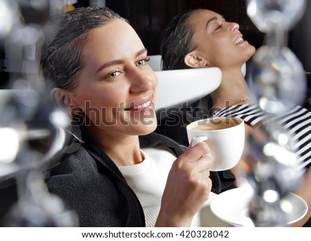 Girl relaxing in the beauty salon with a cup of coffee