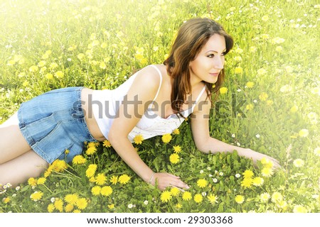 girl relaxing in the grass and flowers - stock photo