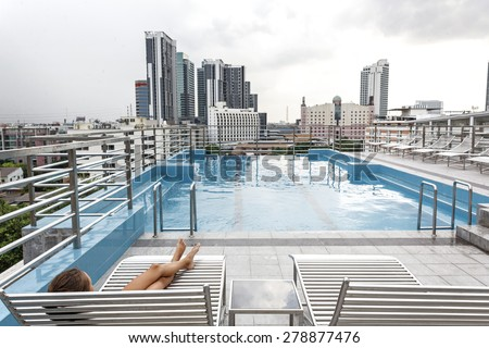 Girl relaxing in the pool on the roof of resort with urban view on skyscraper in Bangkok city