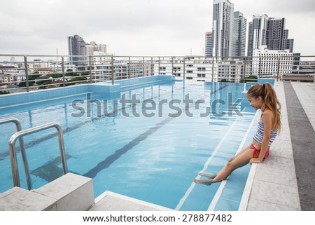 Girl relaxing in the pool on the roof of resort with urban view on skyscraper in Bangkok city - stock photo