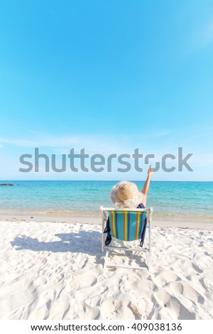 Girl relaxing on chair at beach on very beautiful clear blue sky and clean sea - stock photo