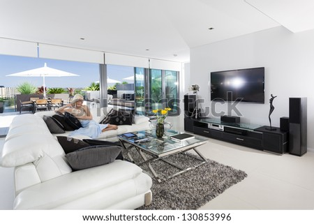 Girl relaxing on couch in luxury living room - stock photo