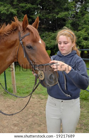 Girl Removing Bridle off her Horse - stock photo